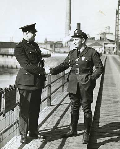 Canadian and American border patrol shake hands at the International Boundary line, 1938.